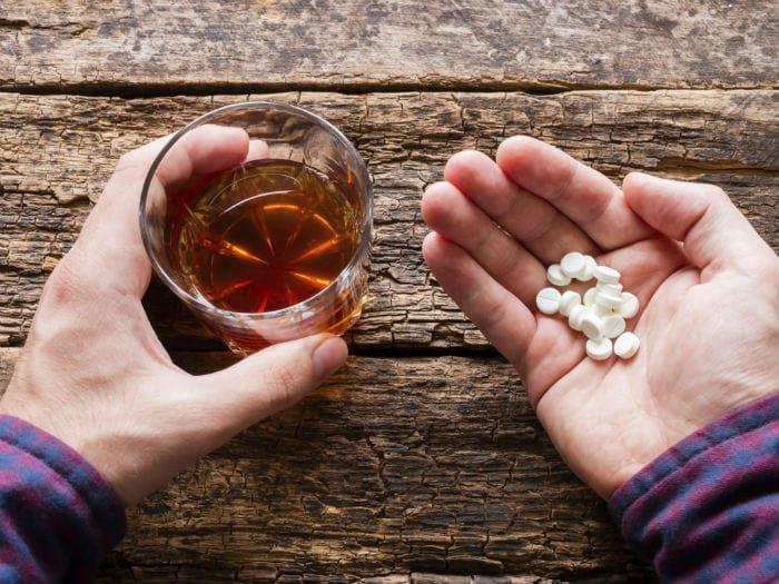 в одной руке алкоголь, в другой таблетки