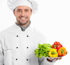 Повар с подносом овощей